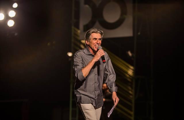 Secretário de Cultura, Guilherme Reis, fala ao microfone durante abertura do 50º Festival de Brasília. Veste camisa de cor grafite e calça bege